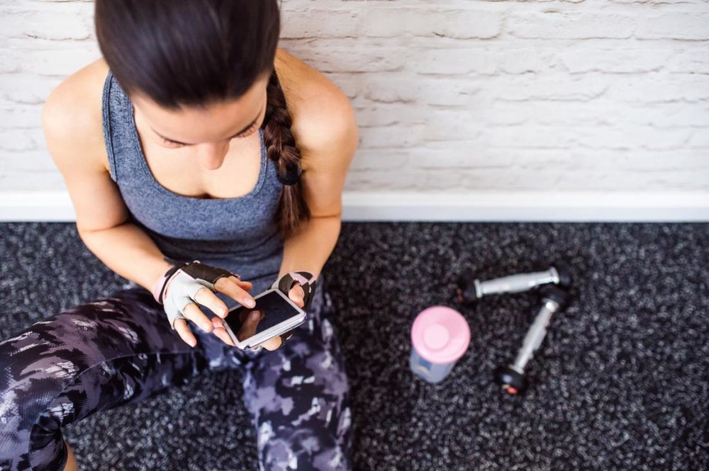 woman-holding-phone-at-a-gym.jpg