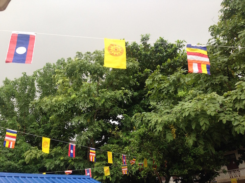 Lao and Buddhist flags strung across Wat Mixai. I iook this photo just before the grey clouds above opened and poured rain