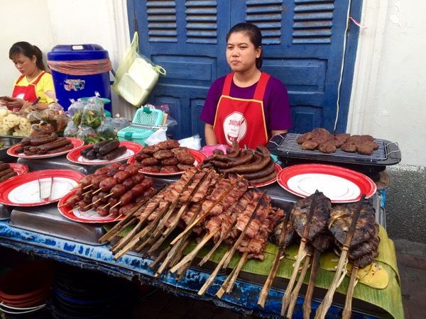 A market stall with skewered pork (amongst other meats), pork intestines and sausages served by a woman in a red apron is a common sight throughout Laos