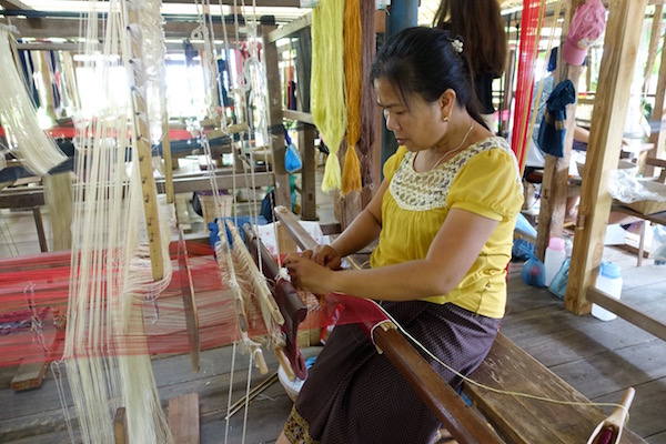 "A Lang Prabang weaver sits at a traditional ""standing loom"""