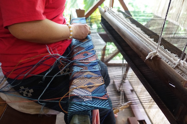 One of the master weavers, Kieng, works on a King Naga wall hanging. It will take her over 150 hours to complete