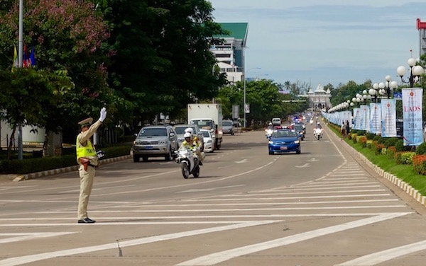Police stop traffic for a motorcade driving up Lane Xang towards Patuxai Monument. The Presidential Palace is in the distance, ASEAN Fever | Eat Drink Laos http://eatdrinklaos.com/blog/asean-fever