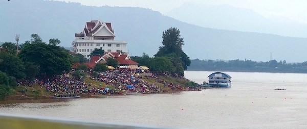 Champasak province in southern Laos in October - cool, rainy and just beautiful. It's also Boat Racing Festival time - and everyone's invited. Crowds wait at the finish line to watch the races | Eat Drink Laos http://eatdrinklaos.com/blog/southern-laos-champasak-boat-racing