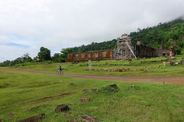 A local Lao boy rides a bicycle past the restoration of the 1,000 year old carved stone structures of Wat Phu, a Khmer Hindu temple ruin, in Champasak, Laos | Eat Drink Laos http://eatdrinklaos.com/blog/southern-laos-wat-phu