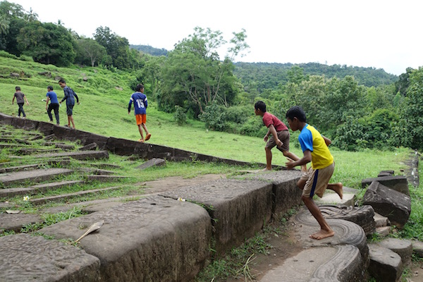 Local Lao kids leap up the well worn, heavy stone steps of the 1,000 year old Wat Phu, a Khmer Hindu temple ruin, in Champasak, Laos | Eat Drink Laos http://eatdrinklaos.com/blog/southern-laos-wat-phu