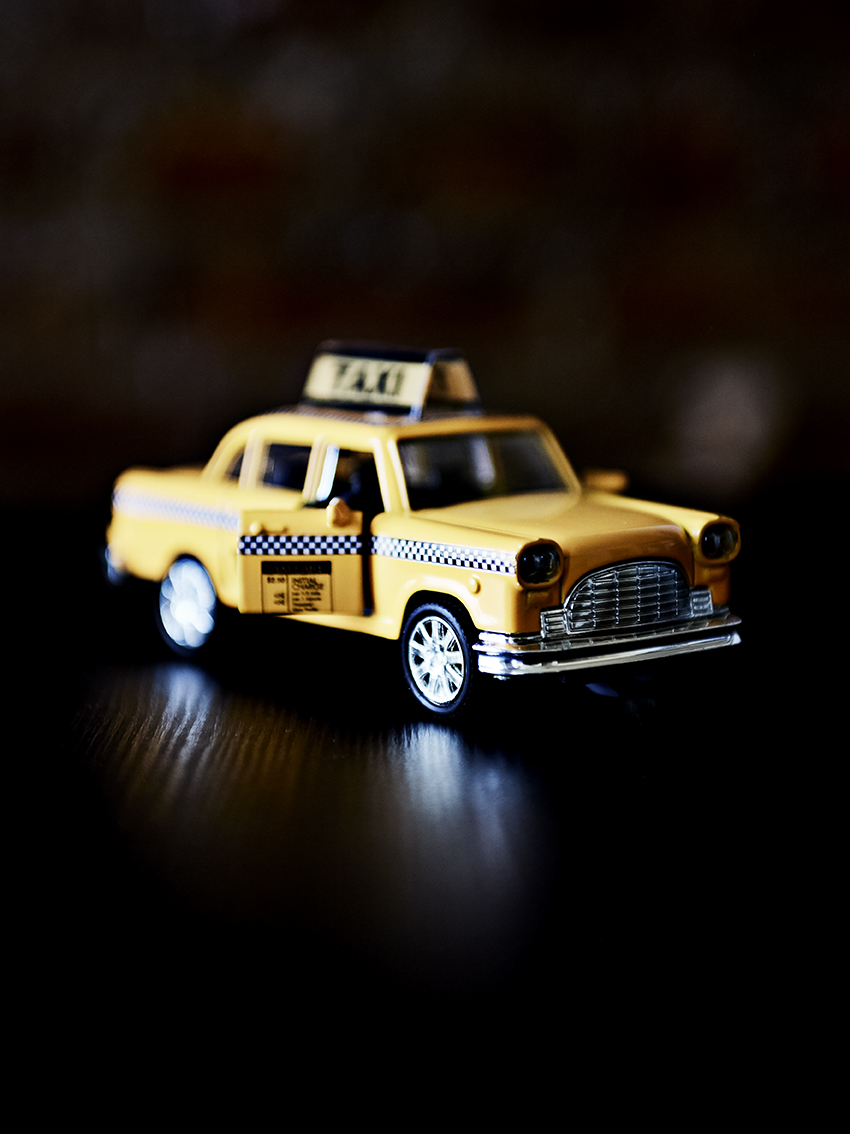 Toy yellow cab in the portrait of Violet.