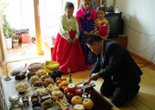 Families gather to feast and honor their ancestors. Sometimes traditional Korean hanbok is worn.