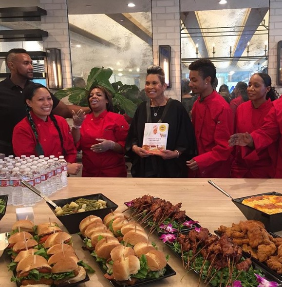 Miss Robbie with her staff holding up her new cookbook