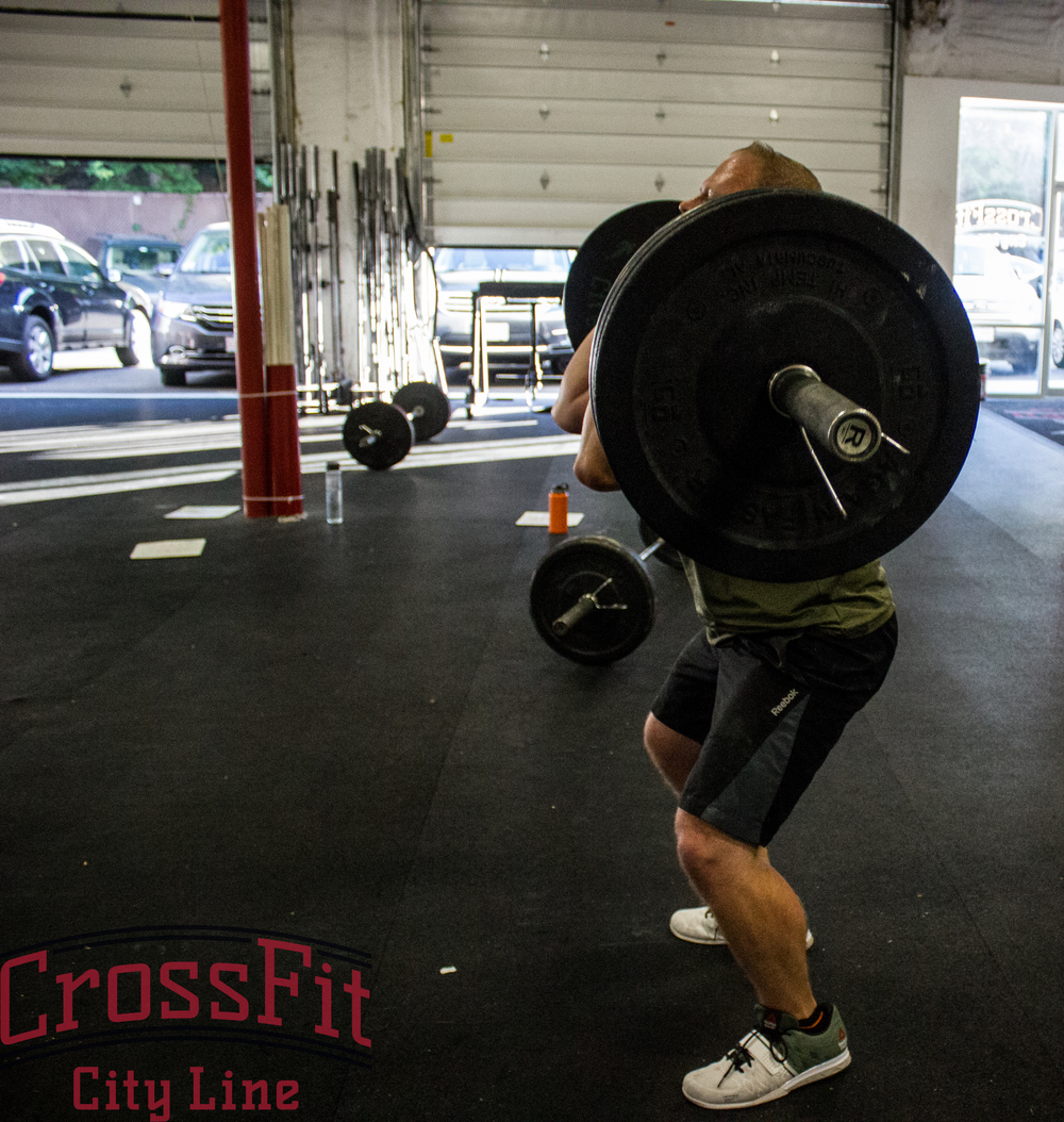 Chris standing up one of many hang squat cleans from Wednesdays partner wod