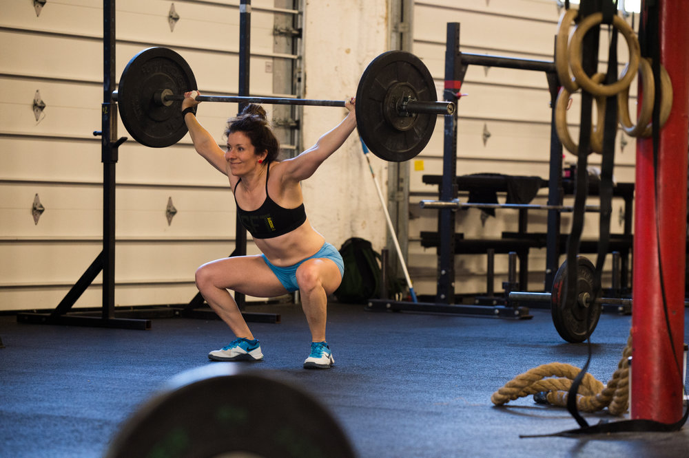 Jaime even smiles as she stands up overhead squats.