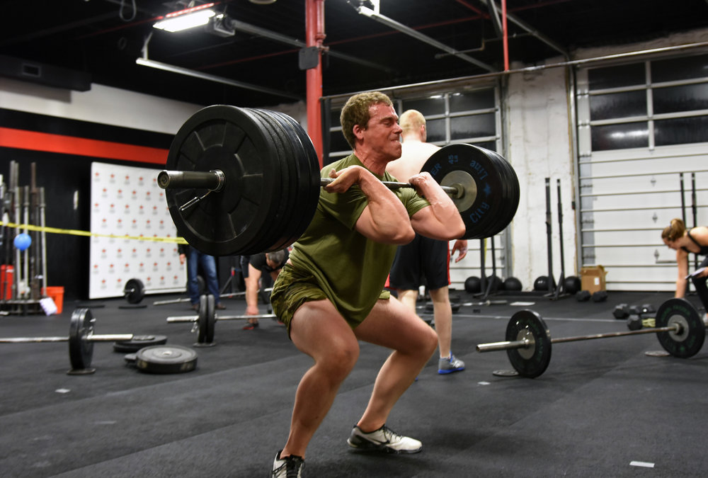 Luke stands up a heavy squat clean.