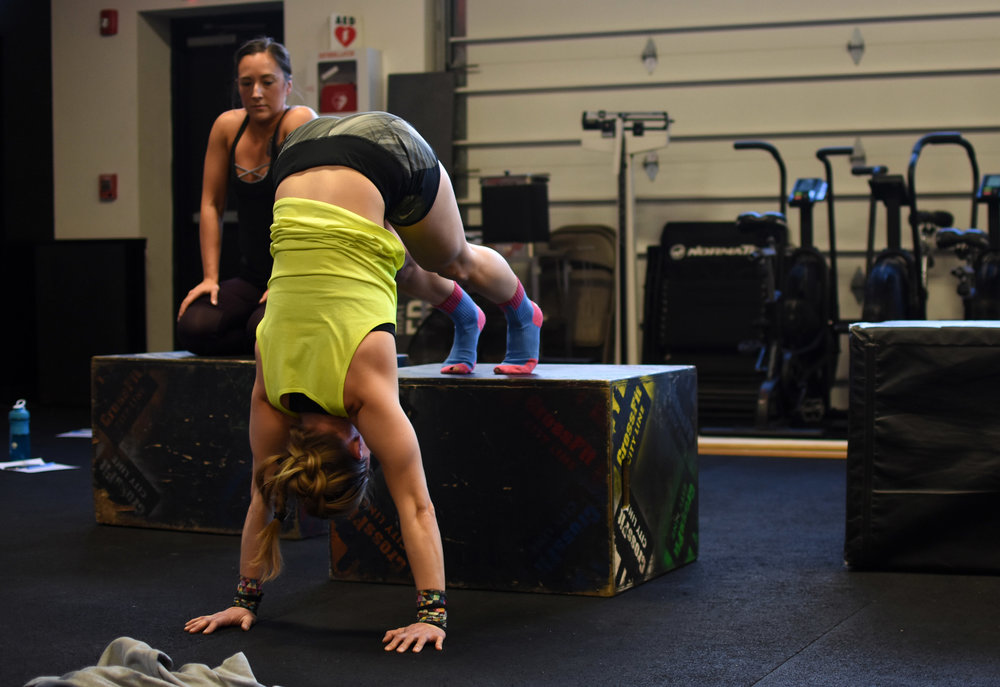The strict handstand push-up has many modifications to build up to a freestanding strict handstand push-up. Each allows athletes to build balance, coordination, shoulder strength, and midline stability. Pictured above is a box handstand push-up!