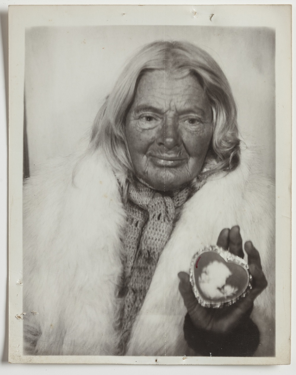 Lee Godie, Untitled (in white fur stole with heart-shaped cameo), n.d.; gelatin silver print; 4 3/4 x 3 3/4 in. Collection of Jim Zanzi, WI.