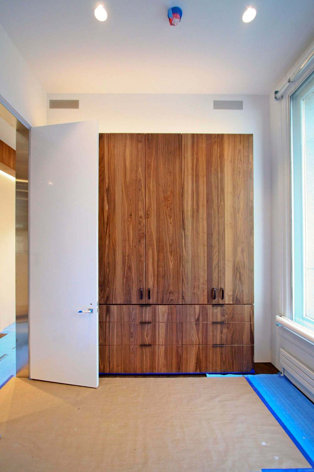 Guest Bedroom  - Built-in Walnut wardrobe and nearly 11-foot tall high-gloss white lacquer door with stainless steel door frame.