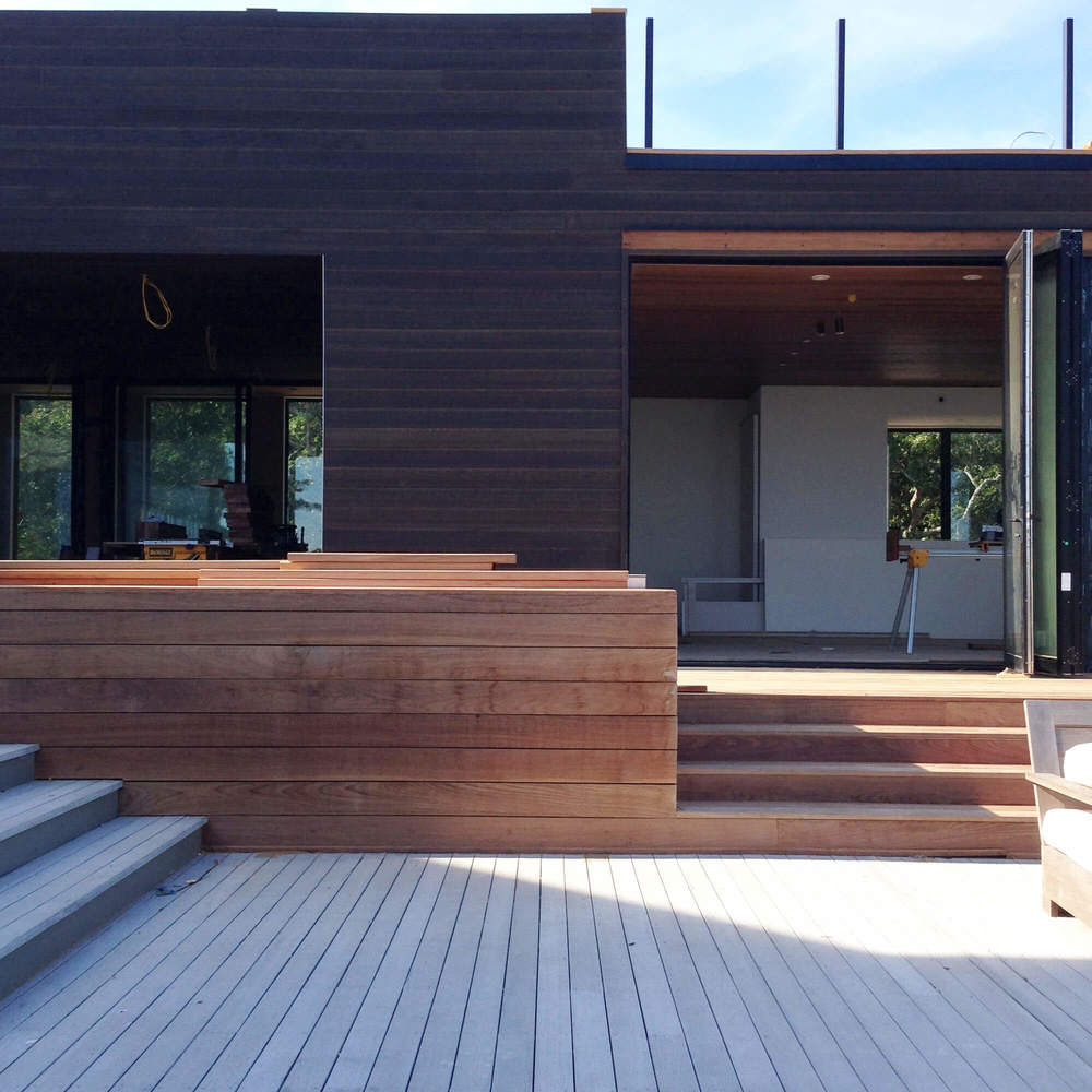 Exterior Bench  -  Ipe bench and risers align with the cedar edge and sliding glass doors beyond.