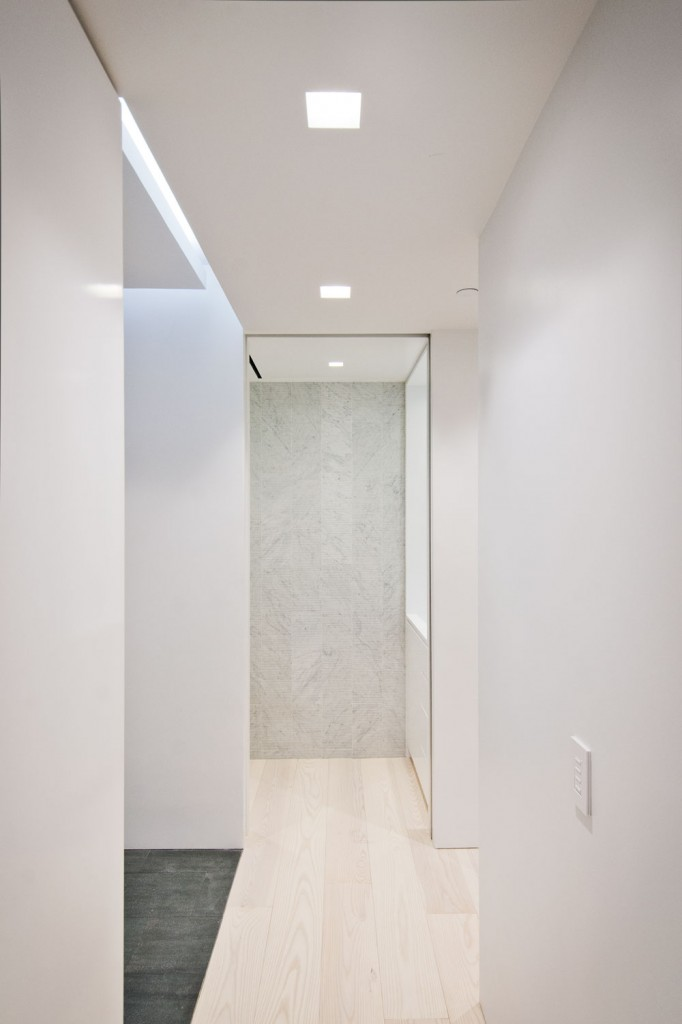 Hallway  -  minimal hallway design with recessed linear lighting strips in soffit and hardwood floors throughout.