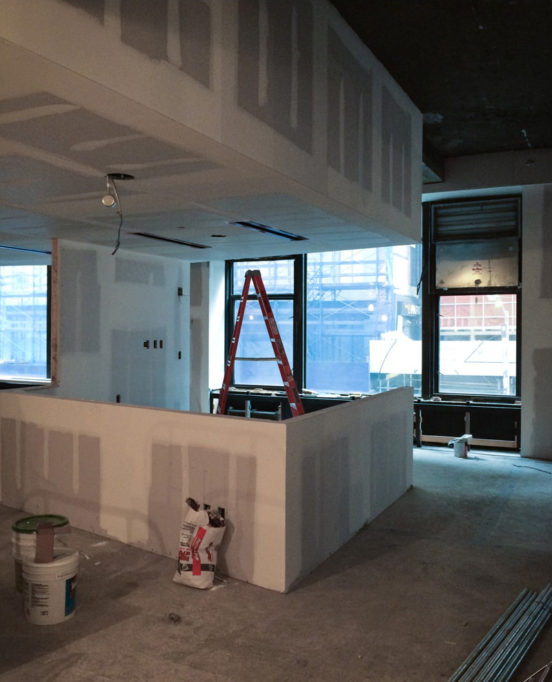 Sheetrock being applied to walls of office space