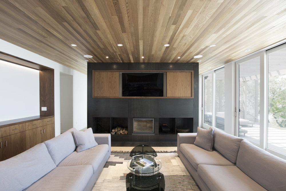 17-res4-resolution-4-architecture-modern-modular-house-prefab-home-north-fork-bluff-house-interior-living-lounge-fireplace-millwork.jpg