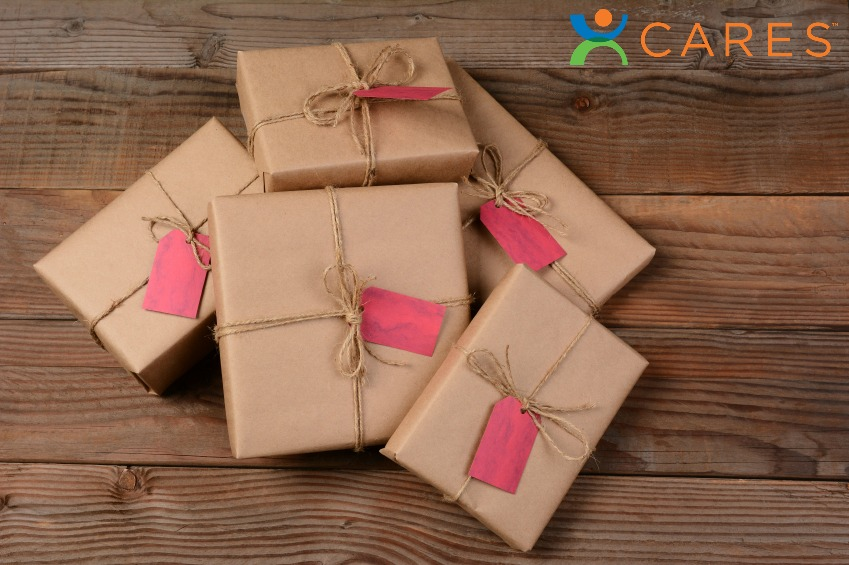 A pileof eco friendly wrapped Christmas Presents, on a rustic wood background.