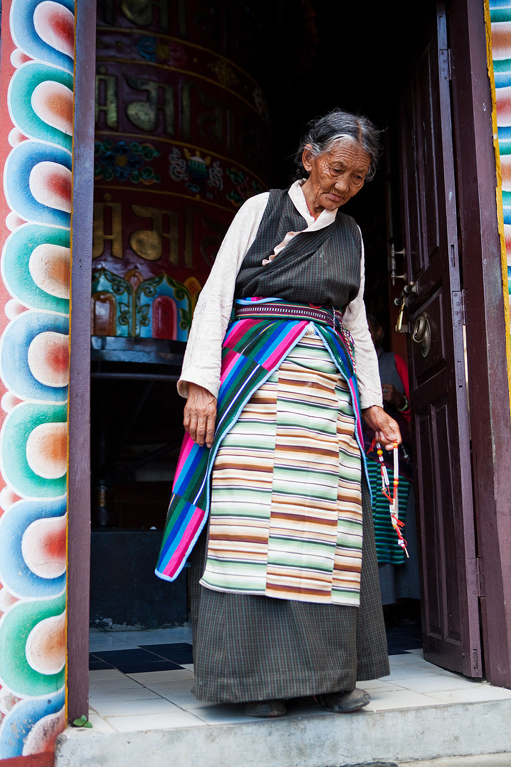 The village elders walk to the monastery to circle the room-sized prayer wheel.