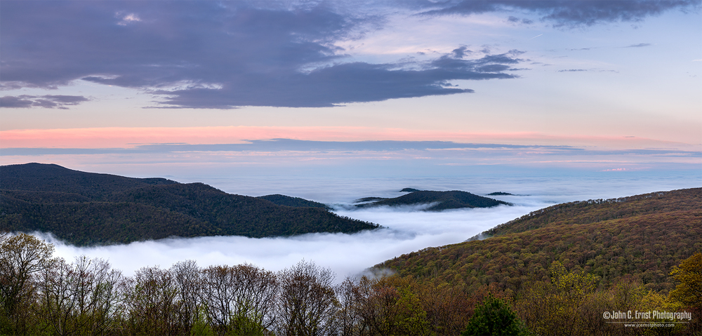 Panoramic of fog in the valley facing east from Skyline Drive at dusk.