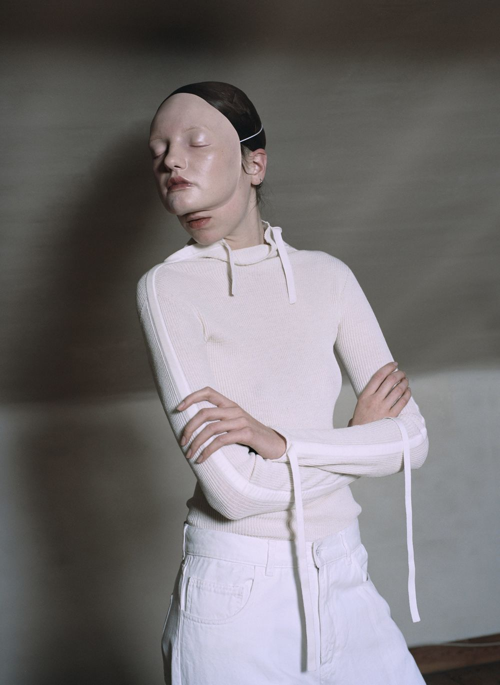 High neck jumper with bone wool silk tapes  CÉLINE,  white denim trousers  JACQUEMUS.