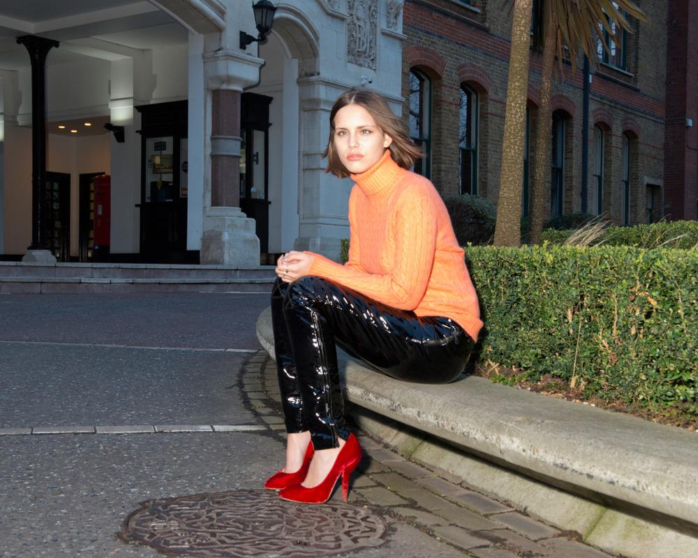 Patent leather trousers  SAINT LAURENT , orange cashmere turtleneck sweater  RALPH LAUREN , red cherry velvet pumps  MIU MIU .
