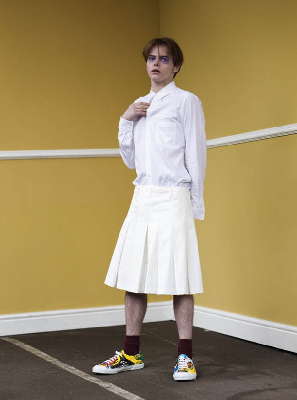 Long white cotton jacket, white shirt with shoulder and back slit details, pleated shorts and hand painted canvas plimsolls.