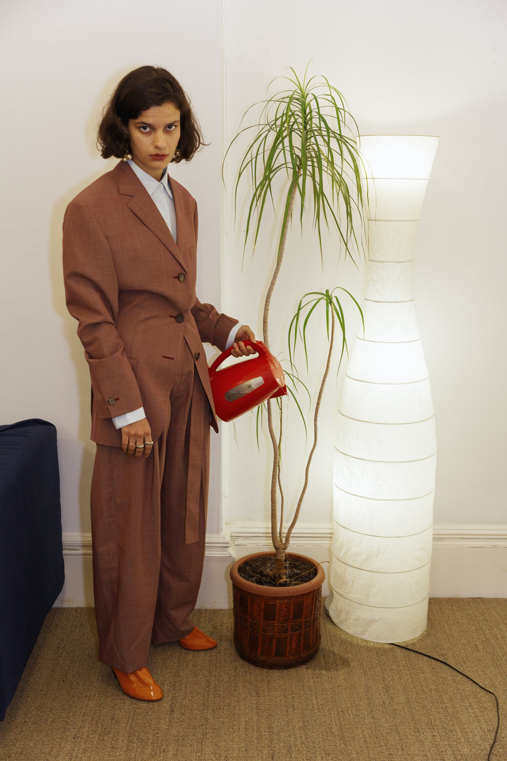 "Brick ""fil a fil"" wool and mohair tailored jacket and high waisted belted trousers, oversize shirt, orange soft patent calfskin pumps and ivory gold dot triple pearl earrings CÉLINE, band gold ring BALENCIAGA, silver ring FESWA."