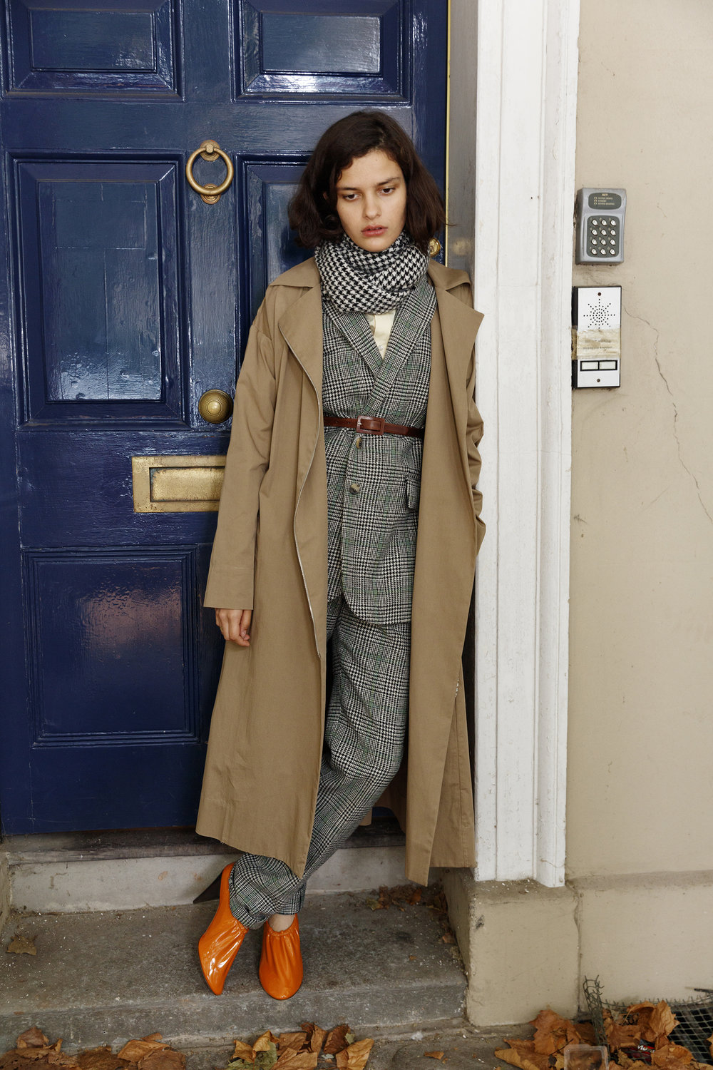 Popeline shirt BALENCIAGA, prince of wales suit and scarf HOLLAND & HOLLAND, crystals encrusted zipped trench coat ISA ARFEN, leather belt FRANCO JACASSI VINTAGE DELIRIUM, orange soft patent calfskin pumps CÉLINE.