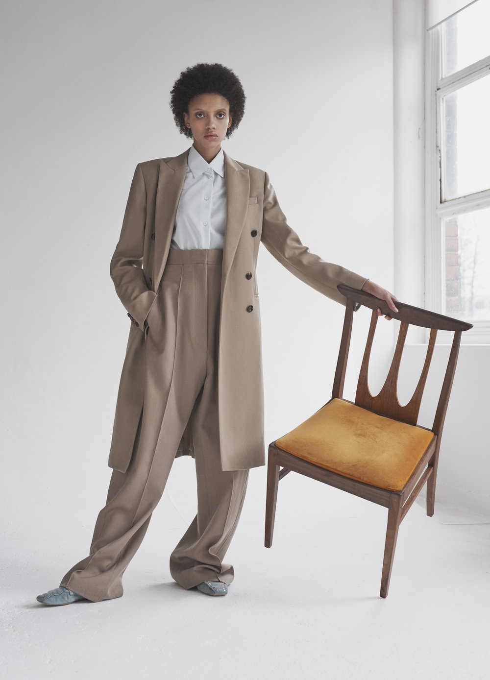 Taupe wool gabardine tailored coat and fluid trousers, jersey oversize shirt and soft moccasin studded loafer CÉLINE.