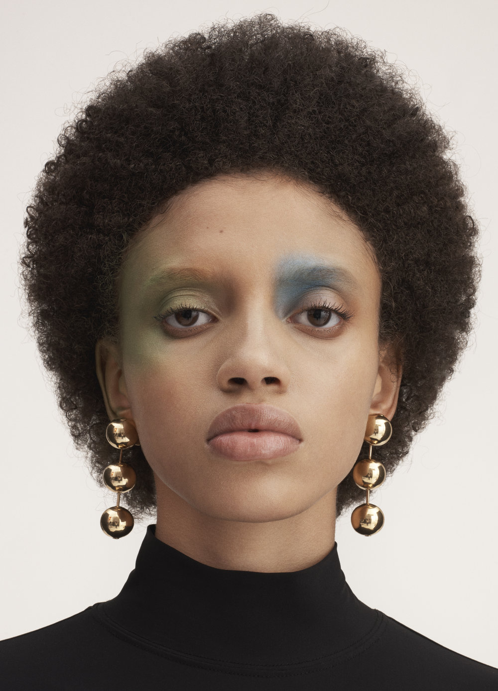 Black turtleneck and gold metal pearl earrings BALENCIAGA.