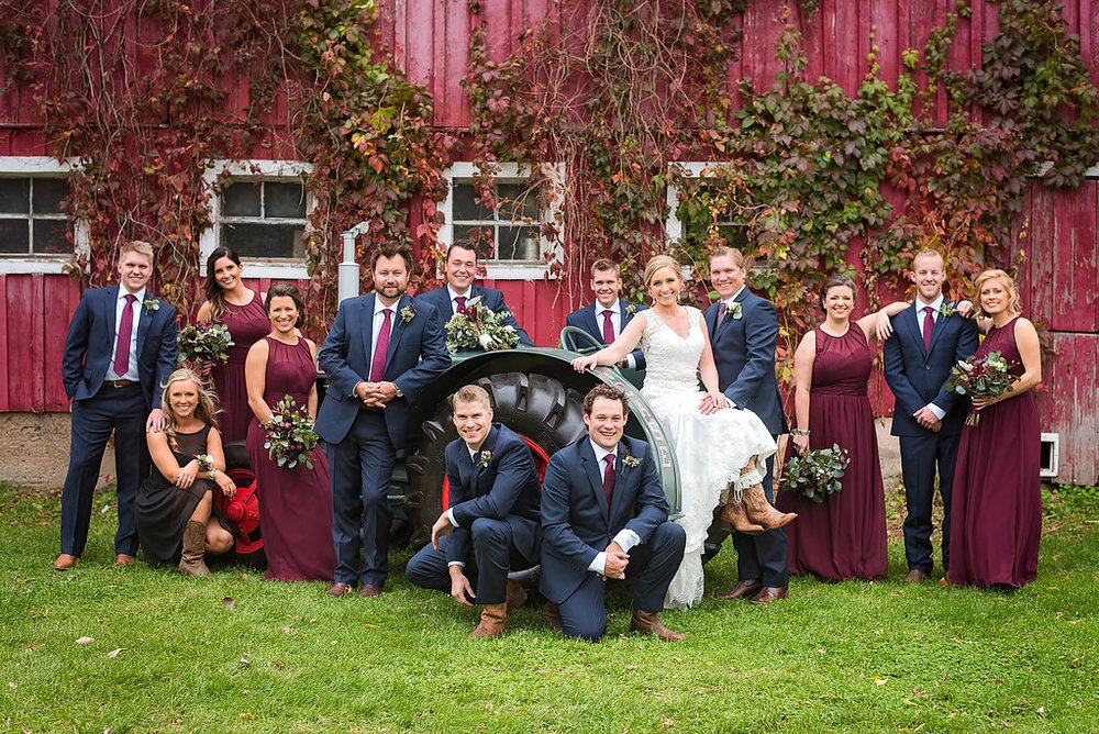 red barn with ivy as wedding backdrop. dark red or crimson bridesmaid dresses. bride with cowboy boots | Kelly Birch Wedding Photographer in Minneapolis St. Paul