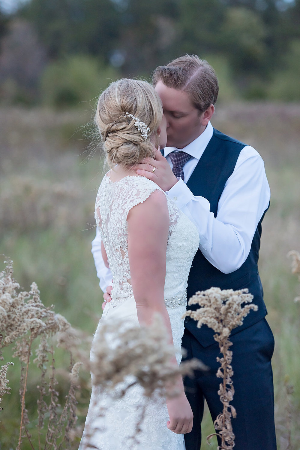 bridal hair piece. bride and groom in a vest kissing in the fields | Kelly Birch Wedding Photographer