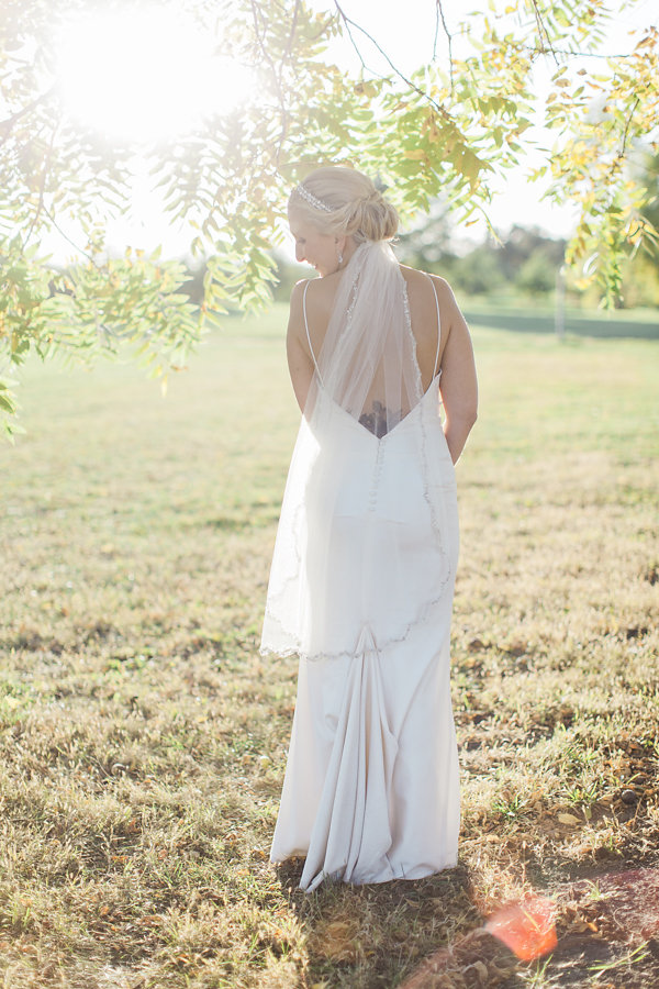 bridal gown with straps and a v plunging back, beaded veil with low hair twist | walking in the orchards | sunlight | Ashley Elwill Minneapolis Wedding Photographer