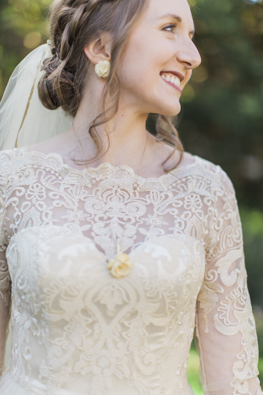 bride in long sleeve lace with sweetheart neckline dress, braided low bun with beaded veil and ivory flower earrings | Ashley Elwill Minneapolis Wedding Photographer