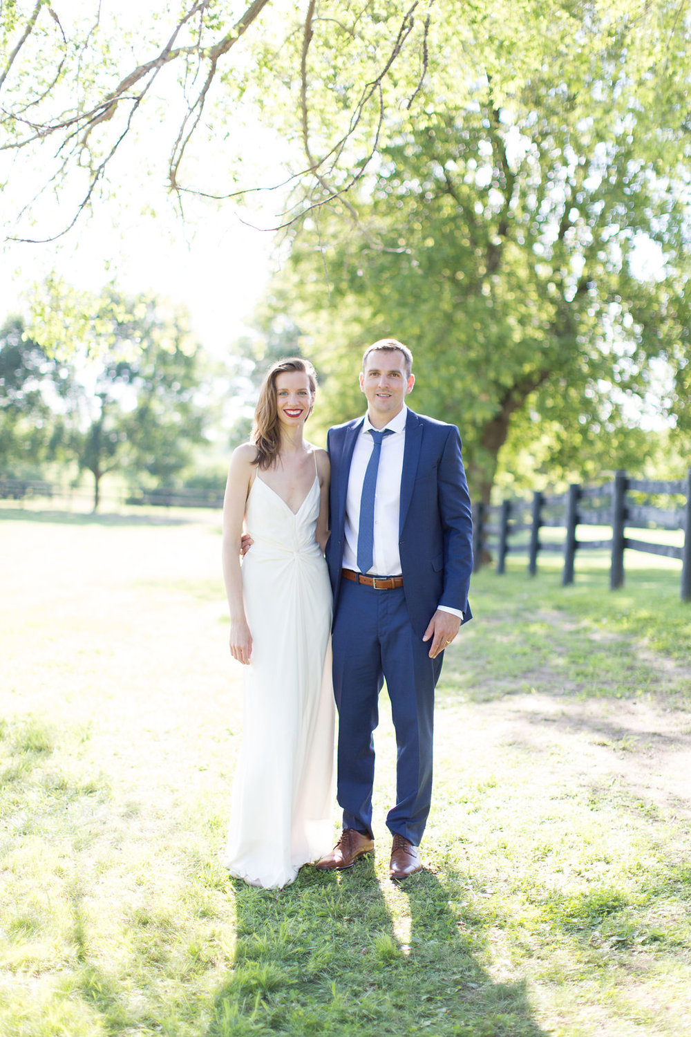 spaghetti strap low v modern wedding dress | groom in navy suit with brown belt and shoes | Ashley Elwill Minneapolis Wedding Photographer