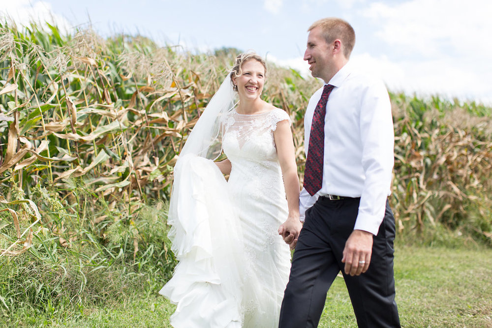 groom in a red striped tie and black pants | beaded lace and see through back wedding dress with long veil | walking in the corn fields | Ashley Elwill Minneapolis Wedding Photographer