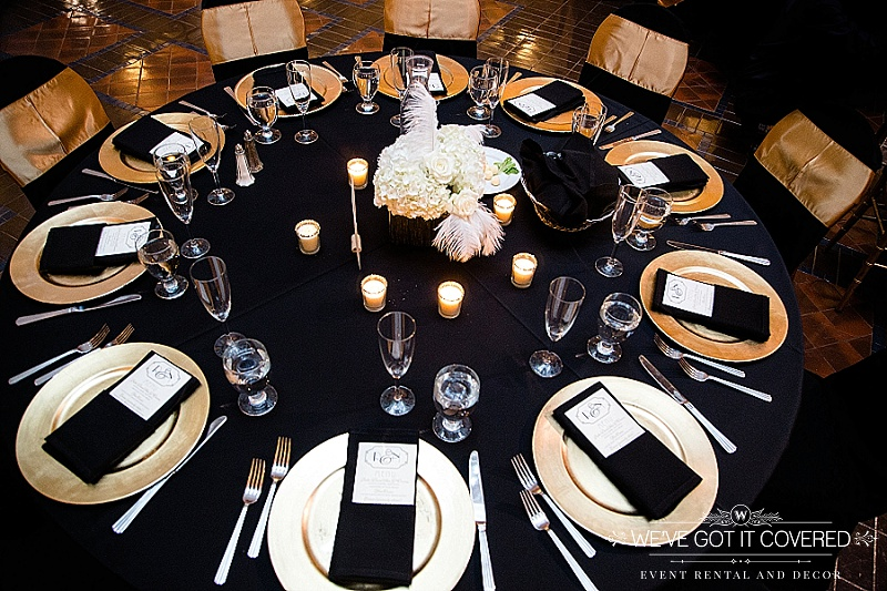 Black napkins menu fold on gold chargers with black table linens and gold chair sashes on black chair covers | centerpiece hydrangeas with roses and white feathers | gold votives | We've Got it Covered