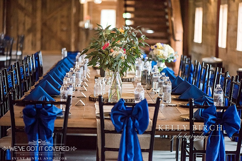 Royal blue triangle napkin fold on gold chargers with blue bow tie sashes on dark brown chiavari chairs with water bottle favors and place settings | floral centerpieces in milk jugs with wood slice and lots of greens | We've Got it Covered | Photo by Kelly Birch Photography