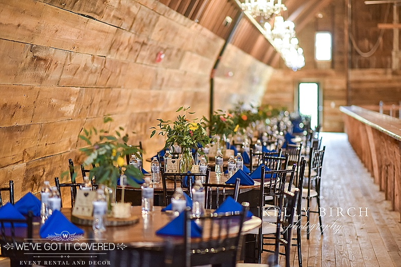 wood slice centerpieces with florals and lots of greenery in milk jug | royal blue triangle fold napkins | dark brown chiavari chairs with white chair pads | We've Got it Covered | Photo by Kelly Birch Photography