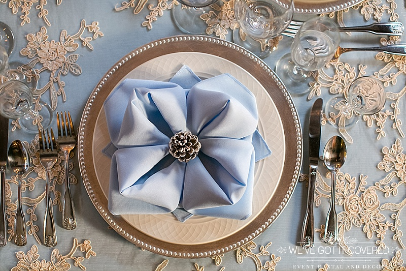 light blue napkin in rose fold with white painted pinecone on gold beaded charger with light blue table cloth and a lace overlay | We've Got it Covered
