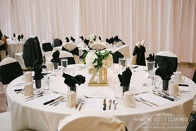 Black flame fold napkins in water glass with white table linen | white chair covers with black bow tie sash | hydrangea centerpiece | We've Got it Covered