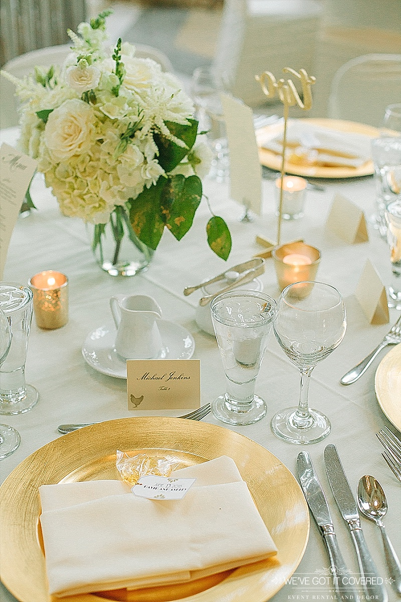 gold charger with ivory menu fold napkin and wedding favor tucked in the fold | table place card with meal option drawing | gold mercury votives | hydrangea and rose centerpiece | laser cut table number in gold | We've Got it Covered