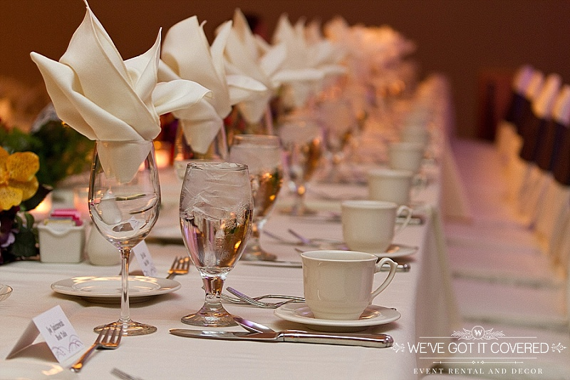 ivory napkin flame fold in wine glass | white table linen with white chair covers and black sashes | We've Got it Covered