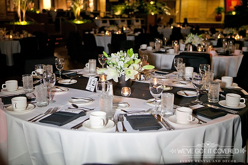 white table linen with dark gray charcoal menu fold napkins and a table runner | lily table centerpiece | We've Got it Covered