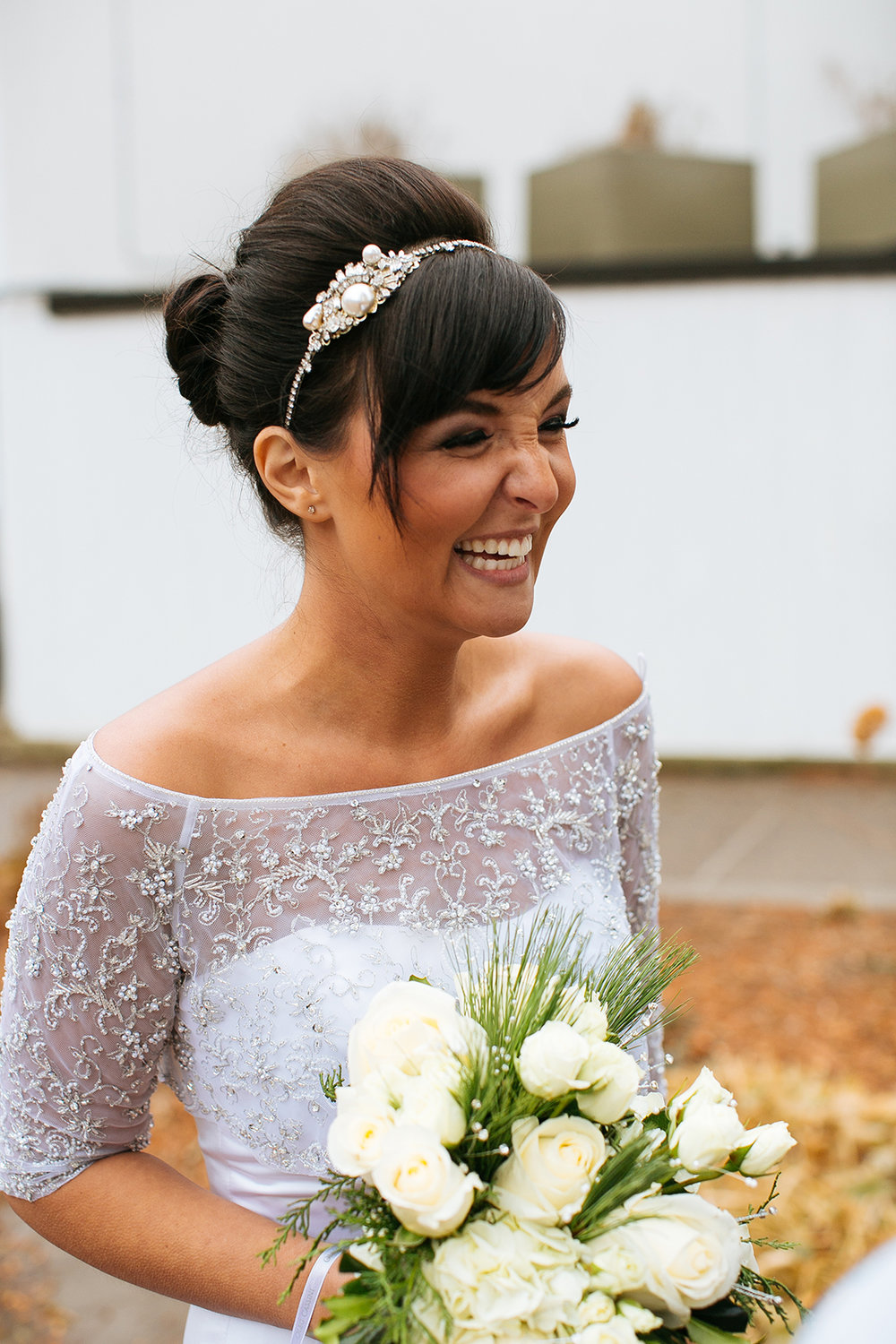 Alyssa Lee Photography | bride laughing with bangs and a bun, off shoulder 3/4 sleeve dress, white bouquet | tan bride | Sixpence Standard Blog | Minnesota wedding