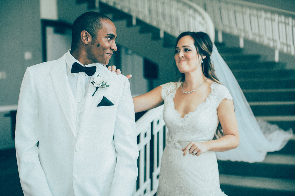 Mark Fierst MN wedding photographer | First look at Calhoun Beach Club | groom in a white suit and a black bowtie with a black pocket square | bride with a cathedral veil