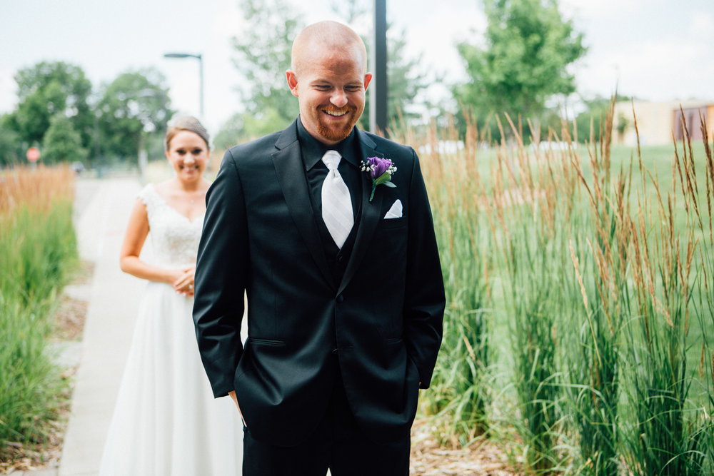 Mark Fierst Wedding Photographer | First Look between the bride and the groom amongst tall grasses | groom in a black suit black button down, black vest and a white on white stripe tie with a purple lisianthus boutonniere