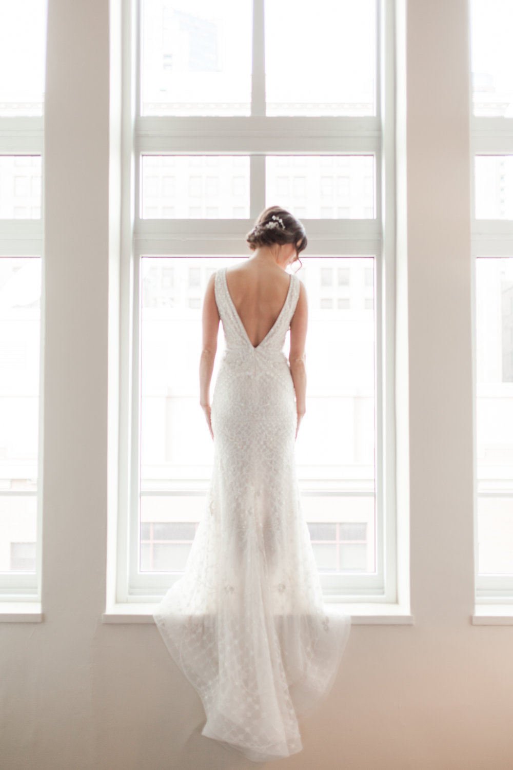 Bride standing in the window | deep v back dress and sheer skirt | Hyatt Place downtown St Paul | Jessa Anderson Photography | Sixpence Events & Planning | wedding blog | winter wedding